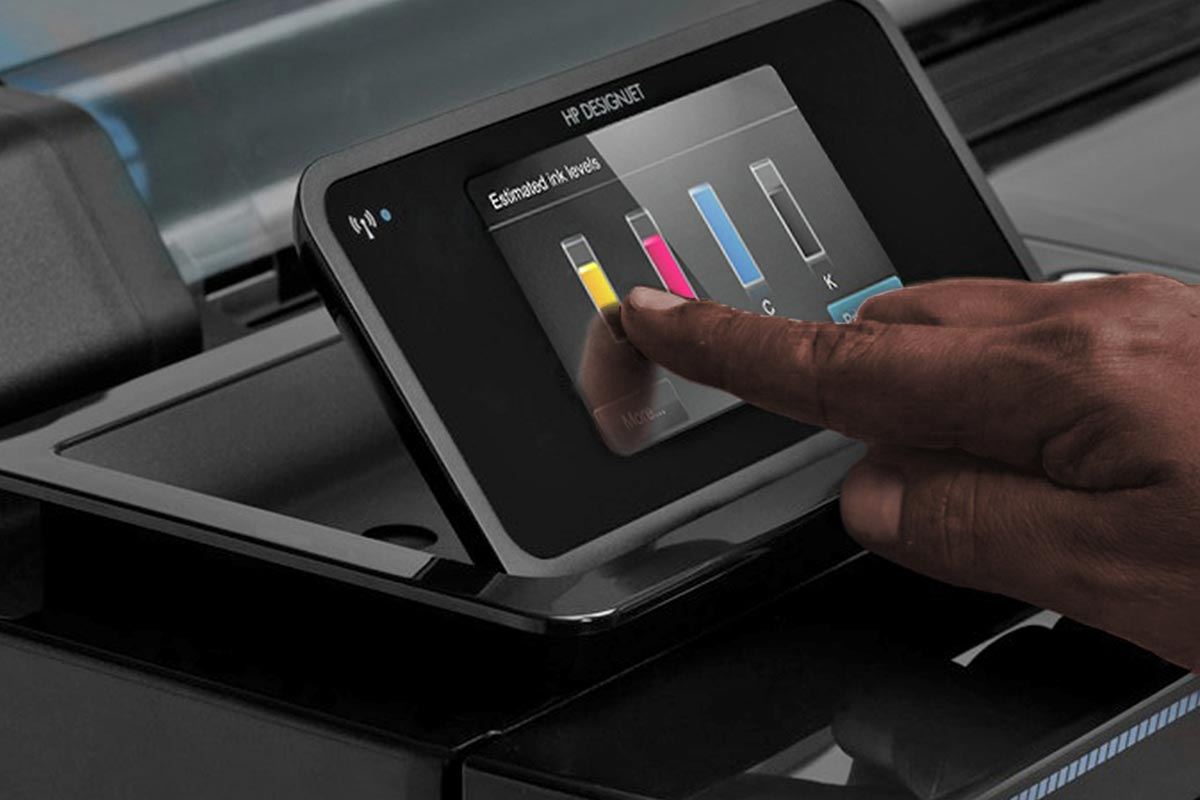 print management – a print operator reaching for the touch screen on an HP Latex printer. Optimise productivity with the Midcomp Pay Per Use (PPU) programme.